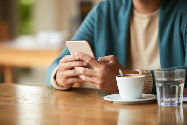 Nie do poznania mężczyzna siedzi w kawiarni z filiżanką kawy i wody i przy użyciu smartfona