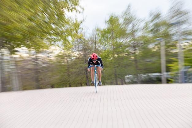 Nie do poznania mężczyzna w kasku w odzieży sportowej, jazda rowerem szybko na chodniku w parku i poczucie prędkości