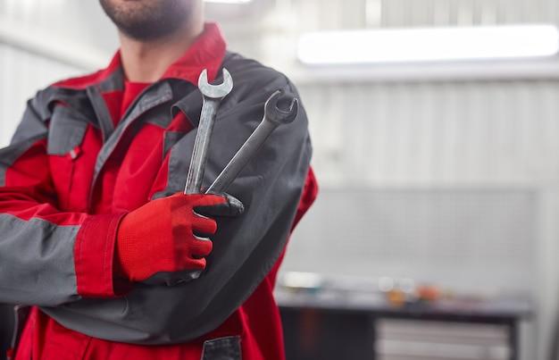 Nie do poznania mężczyzna w mundurze z metalowymi kluczami i skrzyżowanymi ramionami, stojąc na garażu podczas pracy