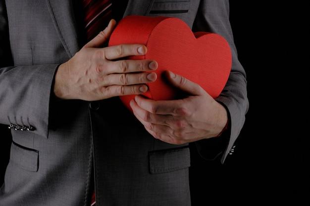Nie do poznania mężczyzna w szarym garniturze wyciąga czerwone pudełko w kształcie serca, gratulacyjna koncepcja, czarne tło