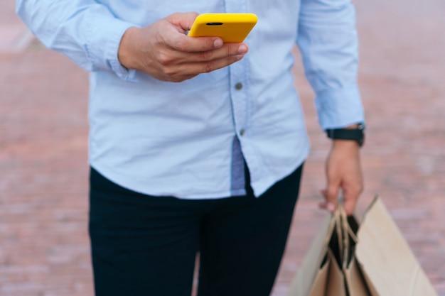 Nie do poznania mężczyzna z torbami na zakupy i telefonem komórkowym w ręku, idąc wzdłuż miejskiej promenady.