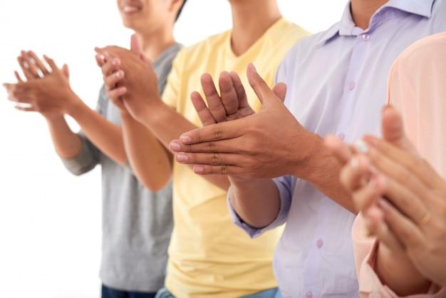 Nie do poznania mężczyźni i kobiety stojące w rzędzie i klaszczące w dłonie