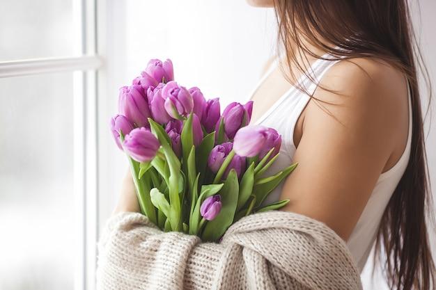 Nie do poznania młoda kobieta trzyma kwiaty w pomieszczeniu
