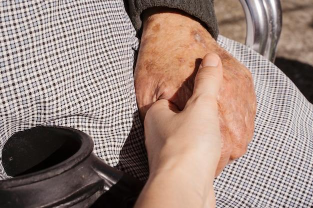 Nie do poznania młoda kobieta, trzymając ostrożnie rękę babci. koncepcja miłości do osób starszych. osoby niepełnosprawne w domowym stylu życia przedszkola. dom spokojnej starości dla osób w wieku geriatrycznym.