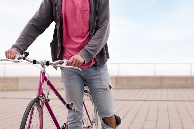 Nie do poznania młody człowiek chodzący z rowerem vintage