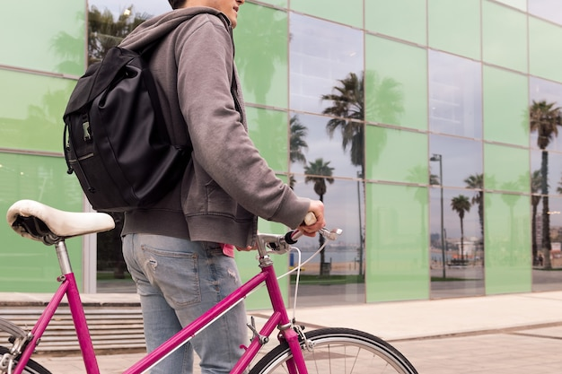 Nie do poznania młody człowiek chodzący z rowerem