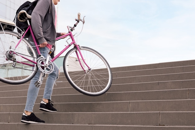 Nie Do Poznania Młody Człowiek Niosący Rower Po Schodach Koncepcja Ekologicznego Stylu życia Premium Zdjęcia