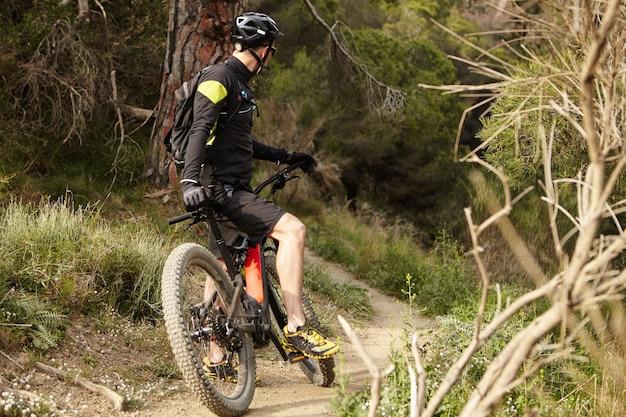 Nie do poznania młody kolarz górski w czarnej odzieży rowerowej trzymający nogę na pedale