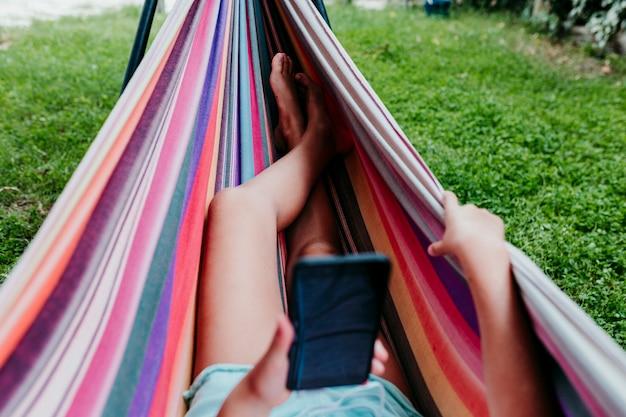 Nie do poznania nastolatka leżącego na kolorowym hamaku w ogrodzie. słuchanie muzyki na telefonie komórkowym i zestawie słuchawkowym oraz uśmiechanie się