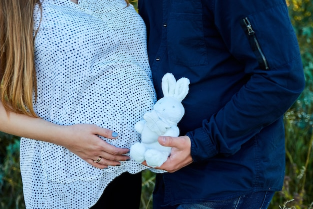 Nie do poznania para dotykająca brzucha i trzymająca pluszowego króliczka