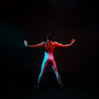 Nie do poznania pełen wdzięku tancerz w trykocie z rozpostartymi ramionami od tyłu