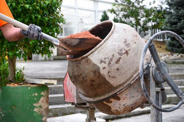 Nie do poznania pracownik budowlany wkładający piasek do betoniarki łopatą.