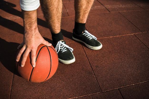 Nie do poznania sportowiec chwytający koszykówkę
