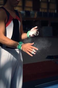 Nie do poznania sportowiec przygotowujący się kładąc mu w ręce magnez do wykonywania ćwiczeń gimnastyki sportowej.