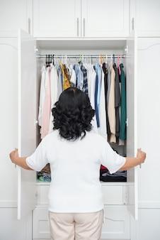 Nie do poznania starsza pani stojąca przed szafą i patrząca na ubrania na wieszakach