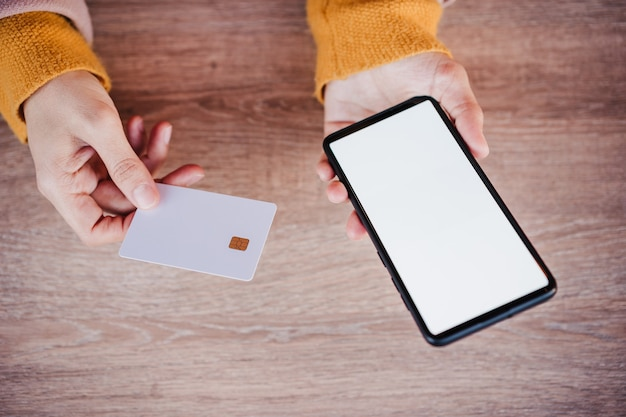 Nie do poznania szczęśliwa kaukaski kobieta na tarasie przy użyciu telefonu komórkowego i karty kredytowej na zakupy online. koncepcja technologii i stylu życia