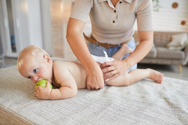 Nie do poznania współczesna mama zmienia pieluchy swojego małego synka, podczas gdy on gryzie zielone jabłko