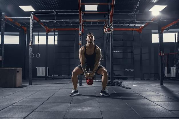 Nie do zatrzymania. młody sportowiec mięśni kaukaski praktykujących przysiady w siłowni z wagą. męski model robi ćwiczenia siłowe, trenuje dolne partie ciała. wellness, zdrowy styl życia, koncepcja kulturystyki.