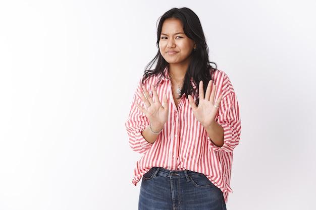 Nie, Dziękuję, Dobrze. Portret Niezręcznej Kobiety Mówiącej Przepraszam, Odmawiającej Oferty, Machającej Niechętnie Dłońmi W Pobliżu Klatki Piersiowej, Uśmiechającej Się I Potrząsającej Głową W Negatywnej Odpowiedzi, Pozującej Na Białej ścianie Darmowe Zdjęcia