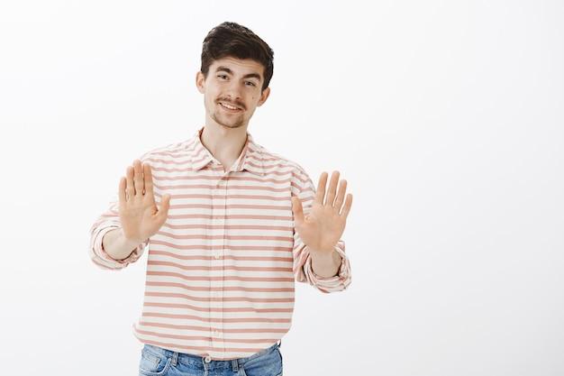 """Nie, dziękuję, odrzucam. portret obojętnego przystojnego brodatego faceta, wyciągającego dłonie w geście """"nie"""" lub """"stop"""". odrzucenie oferty, brak zainteresowania i uprzejmość, stanie"""
