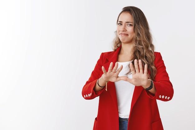Nie, dziękuję, zdaję. portret niezadowolona dziewczyna wyrażająca niechęć antypatia niechęć machanie dłońmi odmowa, gest odrzucenia grymas rażąco niechętna oferta zniesmaczona, biała ściana