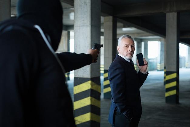 Nie dzwoń na policję. poważny, niezadowolony biznesmen z problemami, trzymając telefon komórkowy i dzwoniąc pod groźbę