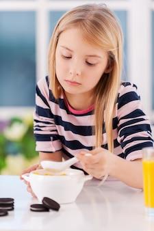 Nie jestem głodny. smutna dziewczynka je coś z talerza siedząc przy stole
