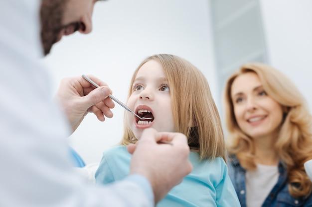 Nie jesteś przerażający. dzielna, aktywna niesamowita dziewczyna siedzi na krześle, podczas gdy dentysta patrzy na jej zęby za pomocą specjalnego sprzętu