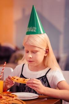 Nie lubić tego. uważna mała kobieta pochyla głowę, patrząc na jedzenie