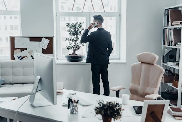 Nie ma czasu na odpoczynek. widok z tyłu młodego mężczyzny w pełnym garniturze rozmawiającego przez telefon