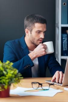 Nie ma czasu na przerwę. przystojny młody mężczyzna w eleganckim stroju casual pracuje na laptopie i trzyma filiżankę kawy, siedząc w swoim miejscu pracy w biurze