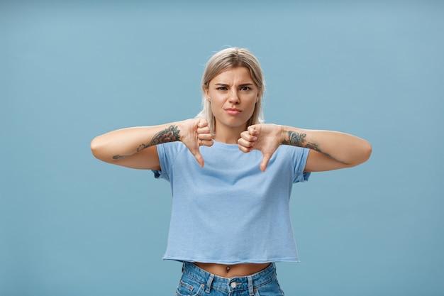 Nie ma mowy, kolega nie lubi. portret niezadowolonej, apodyktycznej artystki tatuażu z tatuażami na ramionach marszczących brwi z niezadowolenia pokazującego kciuki w dół z dezaprobatą stojącą