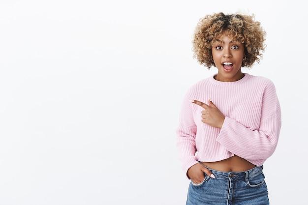 Nie ma mowy, super. portret zaskoczonej i zachwyconej charyzmatycznej młodej afroamerykańskiej fajnej dziewczyny z afro fryzurą z otwartymi ustami ze zdumienia, wskazującą na lewo pytaną i zdumioną