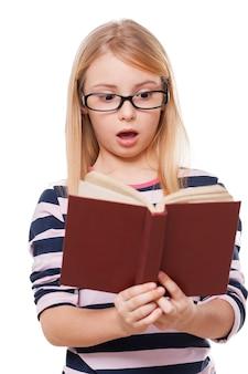 Nie ma mowy! zaskoczona mała dziewczynka czyta książkę i trzyma usta otwarte, stojąc na białym tle