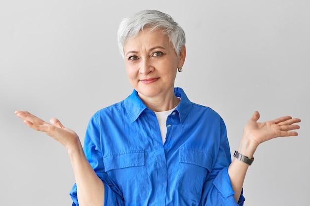 """Nie mam pojęcia. stylowa emocjonalna dojrzała kobieta w średnim wieku z krótkimi siwymi włosami wyrażająca zmieszanie, wzruszająca ramionami, zakłopotana i zagubiona, mówiąca """"nie wiem"""". język ciała"""