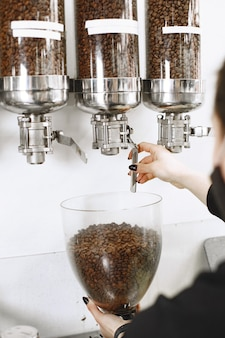 Nie mielona kawa. czarne ziarna. kawa w pojemnikach.