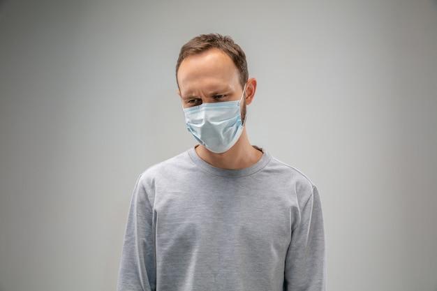 Nie mogę oddychać. kaukaski mężczyzna noszący maskę oddechową chroniącą przed zanieczyszczeniem powietrza i cząsteczkami kurzu przekracza granice bezpieczeństwa. pojęcie opieki zdrowotnej, ochrony środowiska, ekologii. alergia, ból głowy.