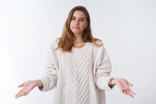 Nie mogę pomóc, nie mój problem. portret nieskrępowana chłód obojętna fajna kobieta ubrana w stylowy luźny sweter rozłożone ręce nieświadoma nie zmartwiona, nieświadoma wzruszająca ramionami uśmiechnięta niechętna pomoc