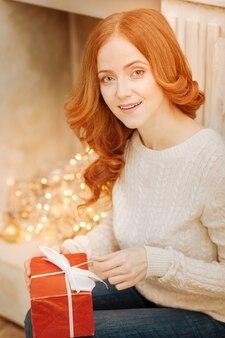 Nie mogę się doczekać, aby go otworzyć. zdumiona rudowłosa dojrzała dama siedząca obok ozdobnego kominka i otwierająca pięknie zapakowany prezent.
