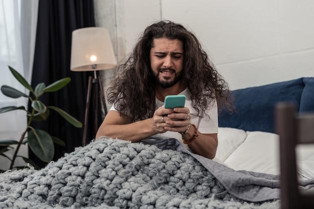 Nie mogę uwierzyć. smutny zestresowany mężczyzna patrzący na ekran swojego smartfona, widząc godzinę