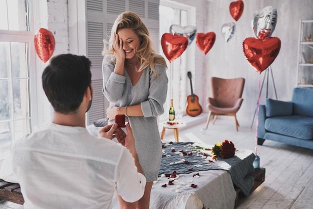 Nie mogę uwierzyć, że to się dzieje! zaskoczona młoda kobieta zakrywa twarz dłonią i uśmiecha się, gdy jej chłopak proponuje ją w sypialni
