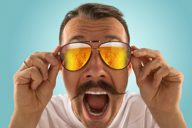 Nie mogę w to uwierzyć. oktoberfest mężczyzna w okularach przeciwsłonecznych pełnych jasnego piwa, patrząc na morze lub ocean alkoholu. wyraz twarzy, zdumiony, szalony szczęśliwy. uroczystość, święta, koncepcja festiwalu.