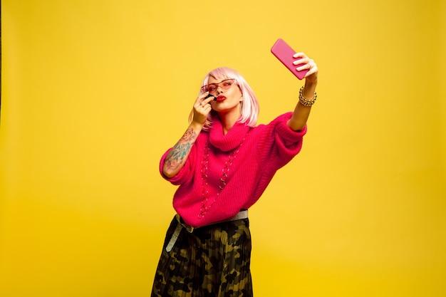 Nie można się nadrobić bez selfie lub vloga. portret kobiety rasy kaukaskiej na żółtej przestrzeni