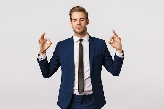 Nie panikuj, kontroluj emocje. spokojny i cierpliwy przystojny biznesmen w klasycznym garniturze, znak zen, rozłożone ręce na boki, zamknij oczy, medytuj, złagodź stres