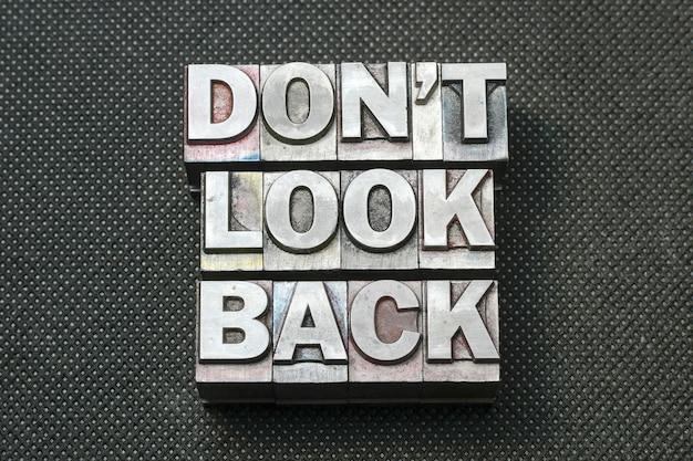 Nie patrz wstecz fraza wykonana z metalowych bloków typograficznych na czarnej perforowanej powierzchni