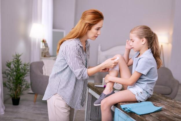 Nie płacz. profesjonalna pielęgniarka patrząc na swojego młodego pacjenta podczas bandażowania jej rany