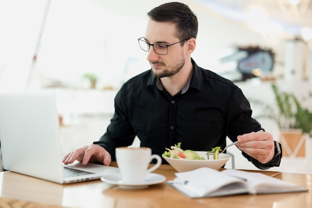 Nie pracuj podczas jedzenia! skoncentrowany mężczyzna z brodą i okularami, ciesząc się świeżą sałatką i wpisując coś na swoim laptopie. praca zdalna z kawiarni. pyszne cappuccino na drewnianym stole.