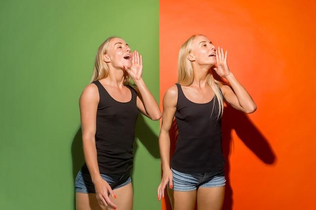 Nie przegap. młode przypadkowe kobiety krzyczą. krzyczeć. płacz siostry emocjonalne krzyczące na tle studia. portret kobiety w połowie długości. ludzkie emocje, koncepcja wyrazu twarzy. modne kolory