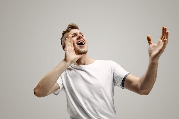 Nie przegap. młody człowiek dorywczo krzyczy. krzyczeć. płacz emocjonalny mężczyzna krzyczy na szarej przestrzeni