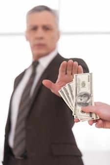 Nie przekupywania. pewny siebie biznesmen z siwymi włosami gestykuluje znak stop, podczas gdy ktoś proponuje mu pieniądze